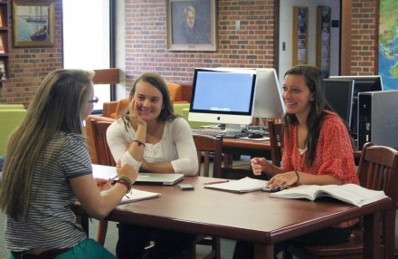 Students conversing at the library during a community free period.